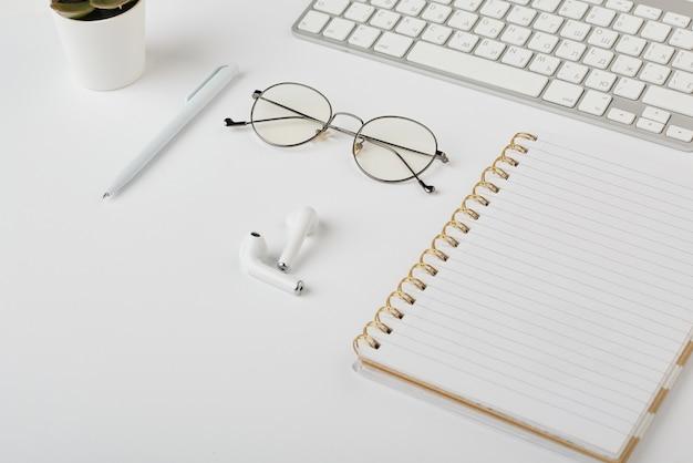 Fones de ouvido sem fio, óculos, caneta, notebook e teclado de computador na mesa branca que é o local de trabalho do gerente de escritório