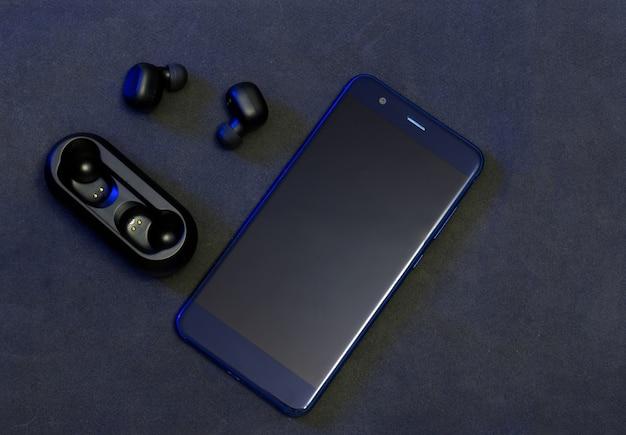 Fones de ouvido sem fio pretos com celular azul em fundo escuro.