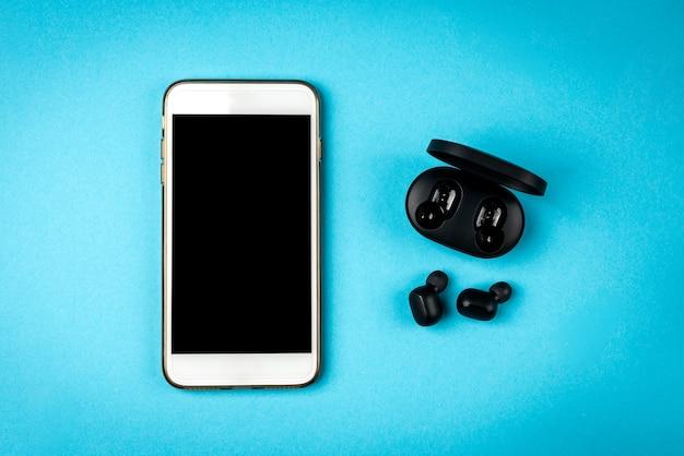 Fones de ouvido sem fio pretos e telefone celular branco sobre fundo azul.