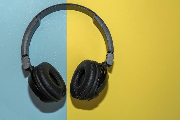 Fones de ouvido sem fio pretos em um fundo duplo de amarelo e azul.