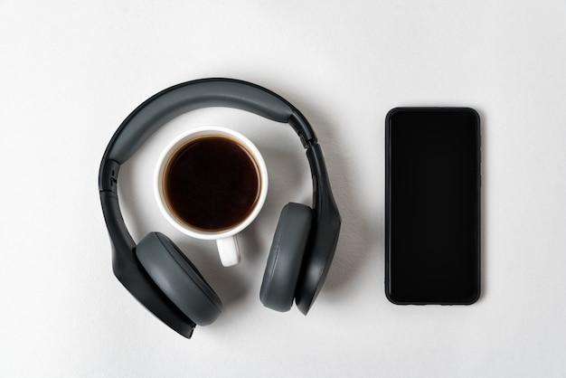 Fones de ouvido sem fio, smartphone e xícara de café em tamanho real. diretamente acima