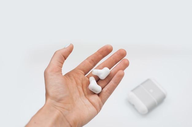 Fones de ouvido sem fio verdadeiros brancos com carregamento caso isolado no fundo branco