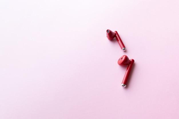 Fones de ouvido sem fio vermelhos em fundo rosa com espaço de cópia