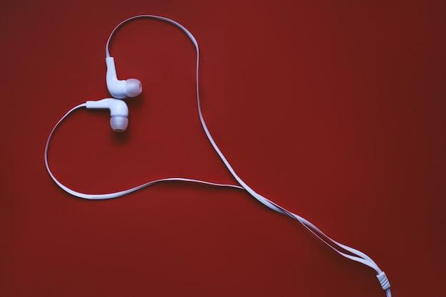 Fones de ouvido sob a forma de um coração em um fundo vermelho.