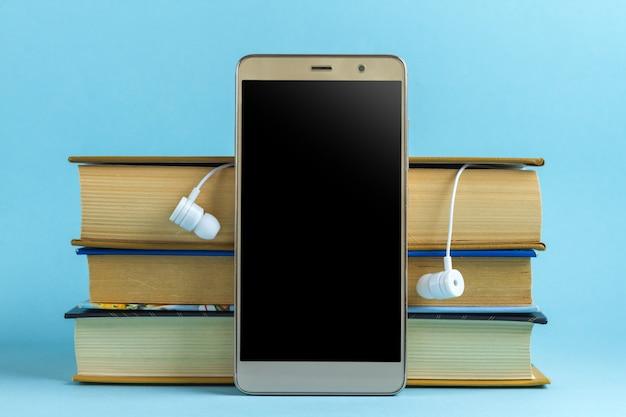Fones de ouvido, telefone celular e livros. conceito de livro de áudio. lendo livros sem levantar os olhos do trabalho