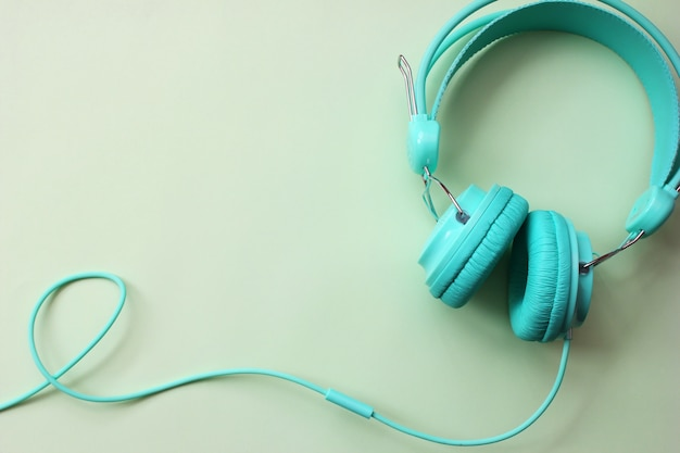 Fones de ouvido turquesa na luz verde