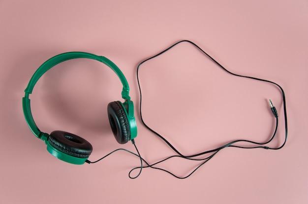 Fones de ouvido verdes em fundo rosa