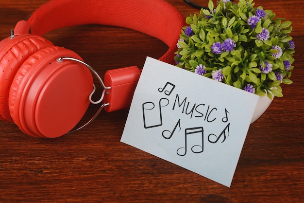 Fones de ouvido vermelhos e papel com