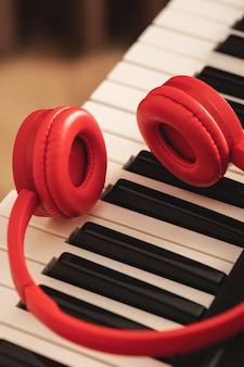 Fones de ouvido vermelhos sobre o teclado sintetizador