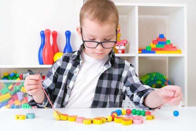Fonoaudiologia, o desenvolvimento de habilidades motoras finas. o menino da criança está amarrando contas em um cordão. criança feliz