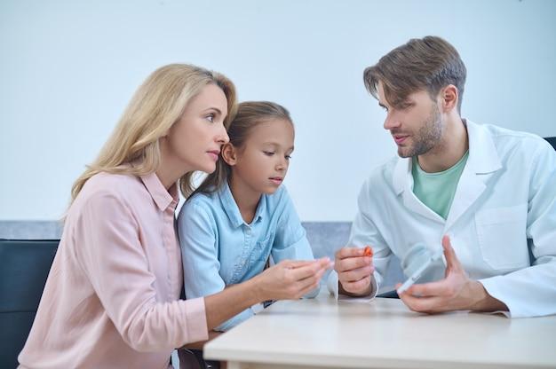 Fonoaudiólogo experiente com um aparelho auditivo na mão, olhando para uma menina e sua mãe
