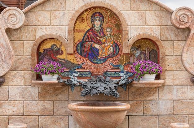 Fonte com flores e imagem em mosaico da virgem maria com jesus cristo