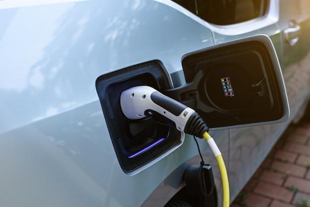 Fonte de alimentação conectada ao carro elétrico moderno sendo carregado