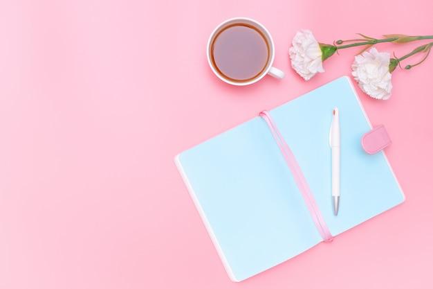 Fonte de escritório de mesa de trabalho, chá quente e flor branca em fundo rosa pastel