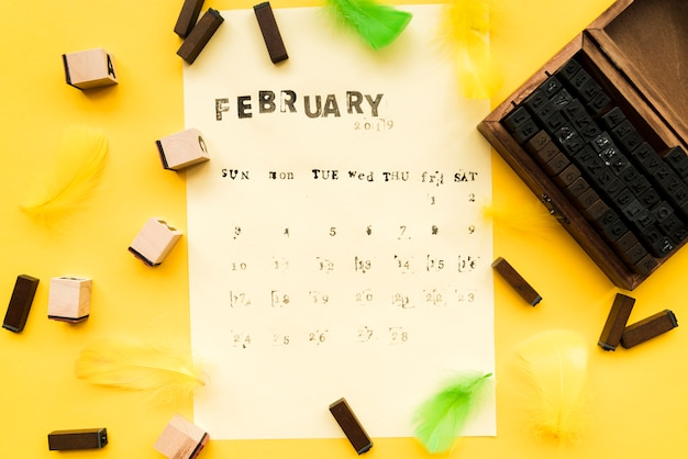 Fonte de máquina de escrever; blocos tipográficos e penas no papel sobre o fundo amarelo
