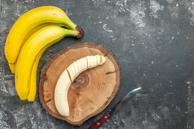 Fonte de nutrição de visão aérea pacote de bananas frescas e picadas em faca de tábua de madeira em fundo cinza