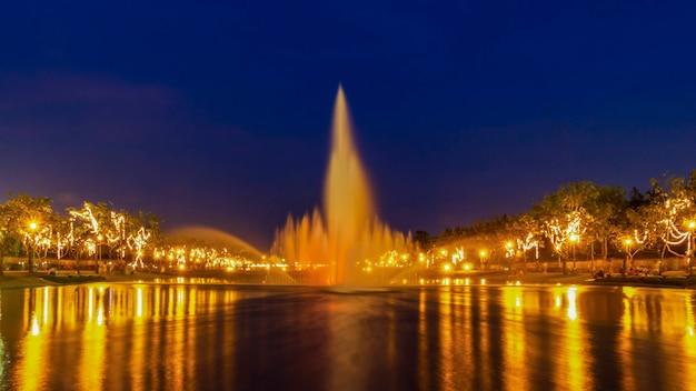 Fonte e reflexão de efeitos da luz na noite, parque em banguecoque, tailândia.