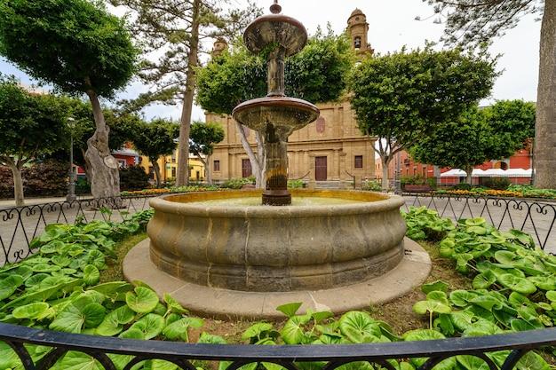 Fonte num parque na gran canaria junto a uma antiga igreja e plantas verdes. espanha, europa,