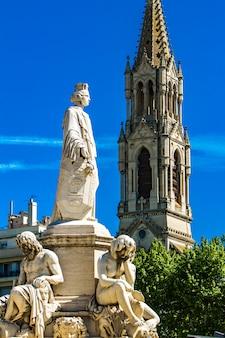 Fonte pradier na esplanada charles-de-gaulle com eglise sainte perpetue em nimes, frança