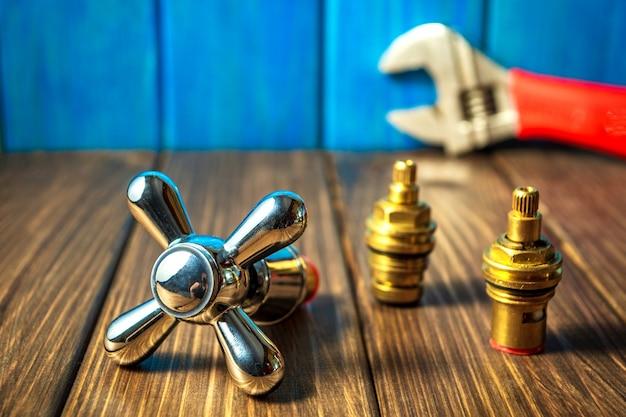 Fontes e ferramentas de encanamento em um fundo azul de madeira e vintage.