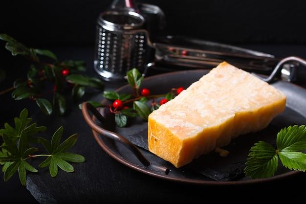 Food concept queijo parmesão orgânico em uma bandeja de ferro rústica sobre fundo de pedra ardósia preta com espaço de cópia Foto Premium