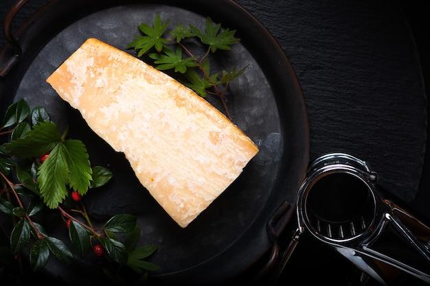 Food concept queijo parmesão orgânico em uma bandeja de ferro rústica sobre fundo de pedra ardósia preta com espaço de cópia