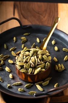 Food spices concept cardamomo ou cápsula de cardamomo em copo de cobre com espaço de cópia