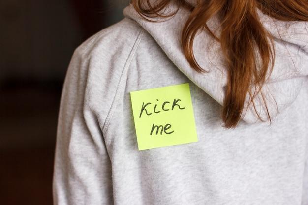 Fool'day jok. adesivo 'kick me' nas costas da garota adolescente.