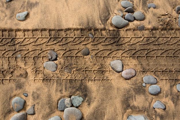 Footpring de pneu de carro em uma praia de pedras de areia