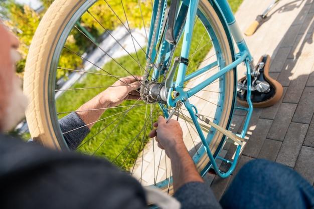 Fora da casa. vista superior de um homem maduro consertando uma bicicleta azul antiquada do lado de fora da casa de verão