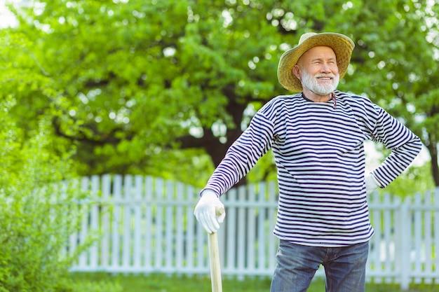 Fora da cidade. homem grisalho sorrindo enquanto aproveita o tempo fora do campo de escavação da cidade
