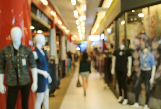 Fora de foco tiro de uma mulher andando no shopping de moda
