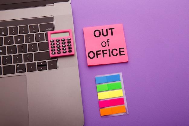 Fora do escritório - mensagem na nota auto-adesiva rosa na mesa de trabalho.