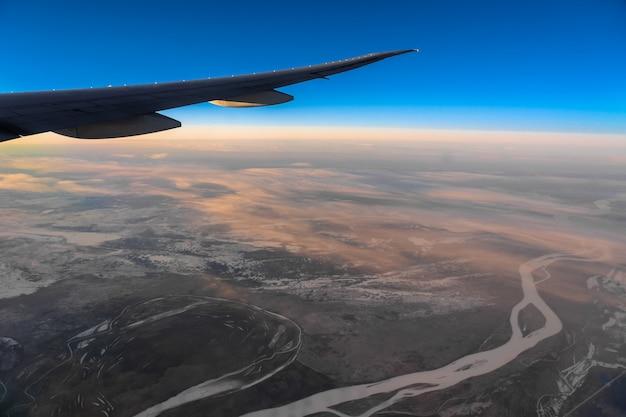 Fora do lado acima da vista das janelas do lado do avião quando nascer do sol, transporte e conceito de viajante