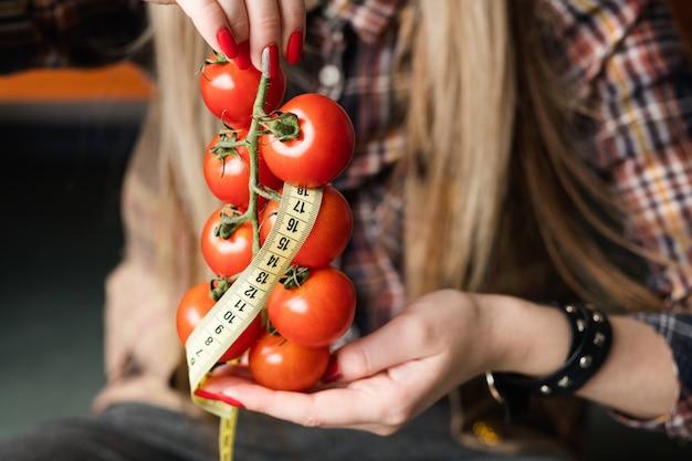 Força de vontade e restrição na luta feminina pela perfeição. mulher segurando tomates frescos com fita métrica torcida na mão.