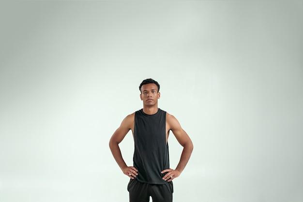 Força e motivação jovem bonito homem afro-americano, mantendo os braços na cintura e olhando para