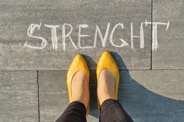 Força, escrita na calçada cinza com pernas de mulher, vista superior