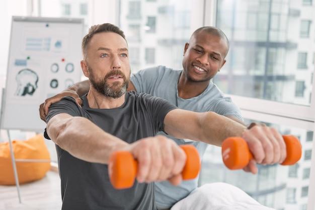 Força física. homem adulto sério segurando halteres na frente dele durante o exercício