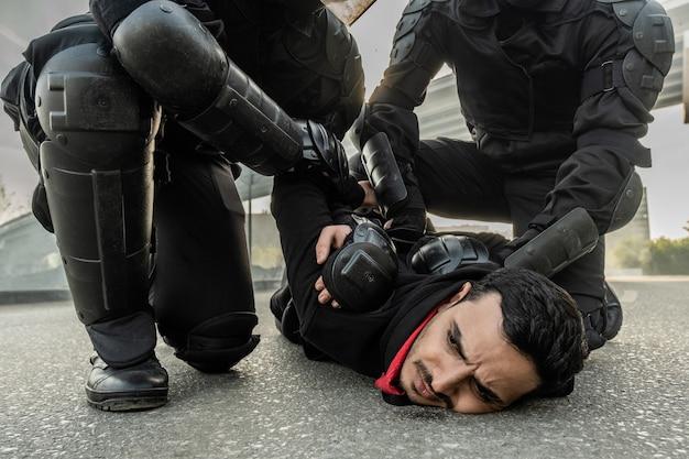 Força motim em traje de proteção pressionando o homem do oriente médio contra o solo enquanto o imobiliza durante o rali