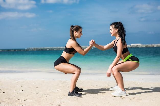 Força no trabalho em equipe. dois atletas de jovens mulheres atraentes exercitam fazendo agachamentos na praia perto da praia