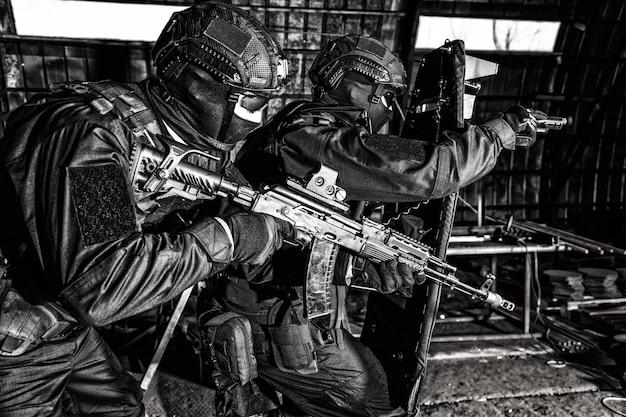 Forças especiais de polícia, lutadores de equipes táticas de contraterrorismo, guardas de empresas de segurança privada apontando armas enquanto avançam sob a cobertura de escudo anti-balístico em ataque antinarcóticos, dessaturados