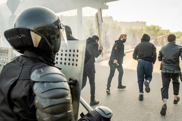 Forças policiais com capacetes segurando escudos antimotim movendo-se para os hooligans em execução enquanto os param na cidade