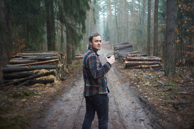 Forester homem barbudo caucasiano, vestido com camisa xadrez, tomando café de uma caneca durante o intervalo entre a floresta nublada e troncos picados