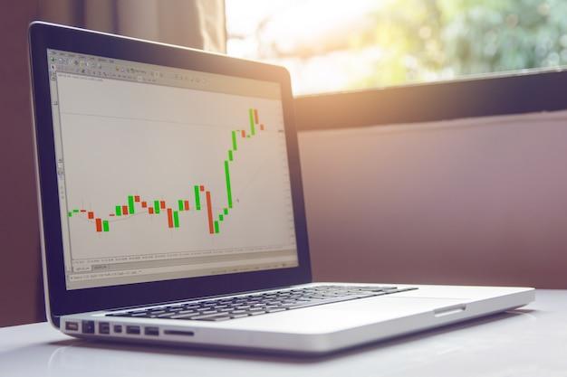 Forex de negociação de ações no laptop em uma mesa branca