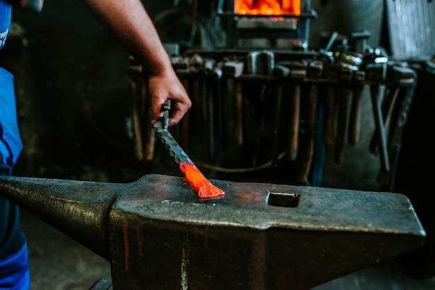 Forjando ferro em brasa com martelo na bigorna.
