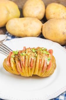 Fork ao lado de uma batata saboroso com presunto