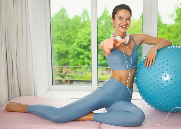Forma atraente fazendo exercícios com uma bola azul
