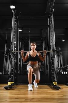 Forma atraente, jovem, esportiva, focada, garota fitness, com, rabo de cavalo, fazendo exercícios de bíceps, enquanto está sentada no banco e levantando halteres na academia à noite
