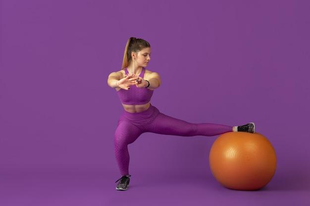 Forma. bela jovem atleta praticando em estúdio, retrato roxo monocromático.