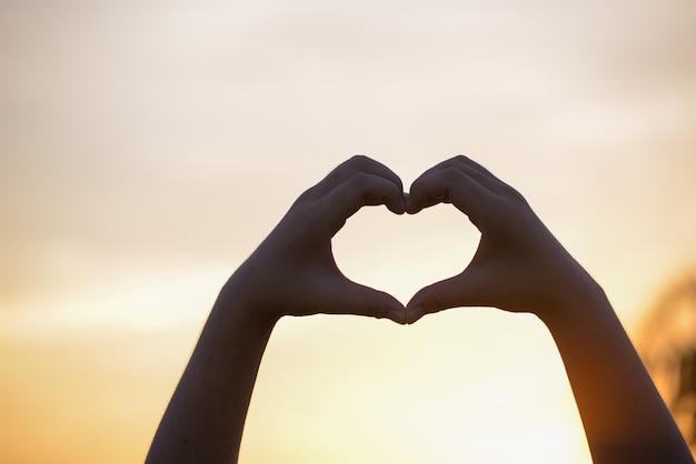 Forma bonita do coração feito à mão da silhueta no fundo do por do sol.